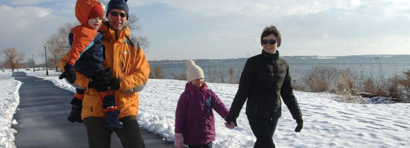 Family walking along Seneca Lake in the Winter